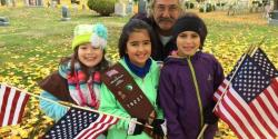 3 smiling young girls holding American flags, man bending down behind them, gravestones in background